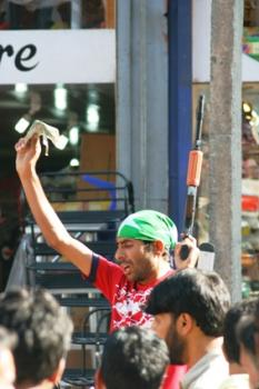 """This photo from """"Etalaat"""" shows a street vendor selling plastic guns in Srinagar's Lal Chowk yesterday, on the eve of Eid"""