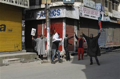 Kashmiri Muslim protesters shout slogans, defying a curfew as one of them, left, holds a photograph of the founder of Jammu Kashmir Liberation Front (JKLF) Maqbool Bhat in Srinagar, India, Monday, Feb. 11, 2013. Sporadic violence left two people dead in Indian-controlled Kashmir despite a curfew that was extended into a third day Monday in the wake of the execution of a Kashmiri man convicted in a deadly 2001 attack on India's Parliament.(AP Photo/ Mukhtar khan)
