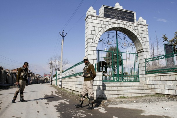 CRPF personnel stand guard at the martyrs' graveyard in Srinagar,preventing entry. The graveyard has a new empty grave, that of Afzal Guru. A similar empty grave waits for Maqbool Bhat, also buried in Tihar jail. Photo credit: Mukhtar Khan/Associated Press