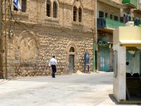 An Israeli settler walking past the military post on Shuhada Street, Hebron.