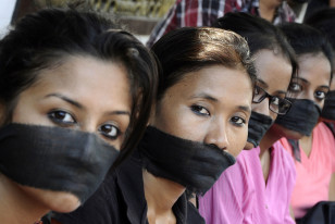 Members of the All Assam Photojournalist Association wear black sashes around their mouths to protest against the rape of a photo journalist by five men inside an abandoned textile mill in Mumbai, in the northeastern Indian city of Guwahati, Aug. 24, 2013. (Reuters)